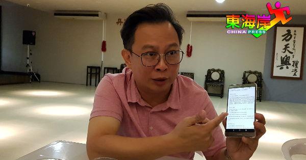 陈祥耀通过智能手机上网查阅关丹中华总商会章程。