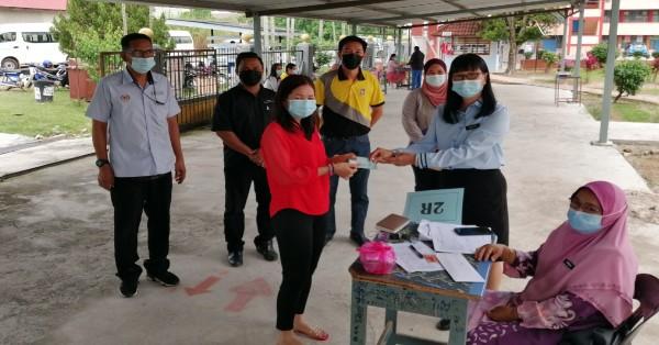 颜玉妹校长(右2)派发援助金给家长,左2起罗斯迪、古志伟。