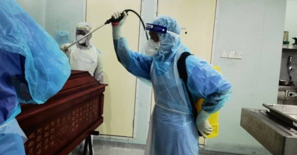 医务人员全副武装,封棺后、喷上消毒液,以防细菌感染。