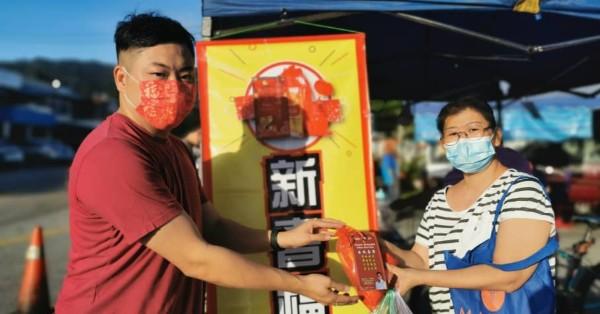 陈咏发(左)派送福袋给市民覃结莲。