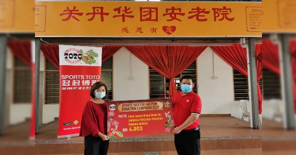 关丹华团安老院副主任陈俐桦(左)从多多博彩代表林家威手中接过善款和购物礼券。