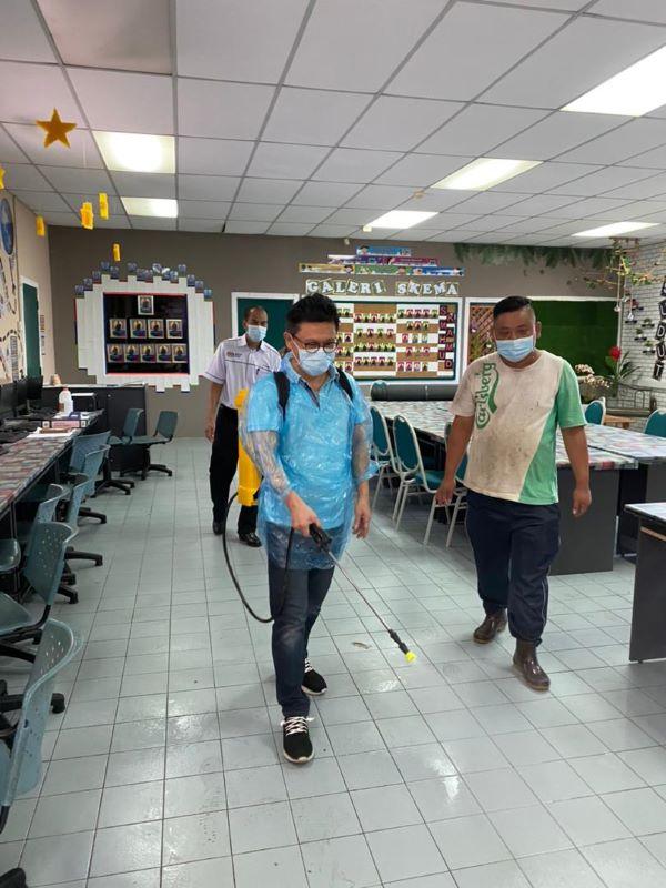 郑联科(左)关心疫情,除了安排消毒队为多间学校消毒,自己也亲自为母校马末国小的电脑室消毒。