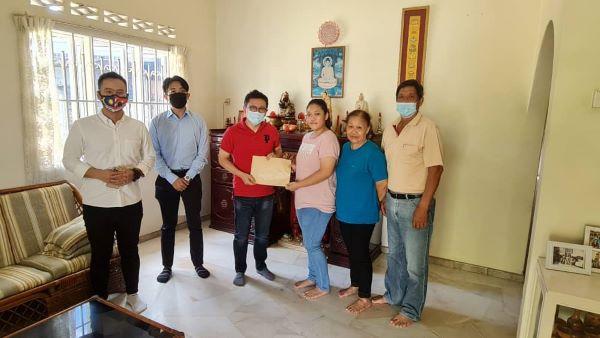 郑联科(左3)亲自将升学助学金批文,交给受惠学生,让后者感动。