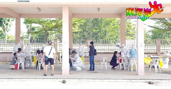 关丹巴耶勿沙政府诊所拭子筛检专区医务人员为幼童进行筛检采样。