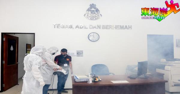 身穿个人防护装备的消毒特工队志工,为阿益布爹警局进行全场消毒工作。
