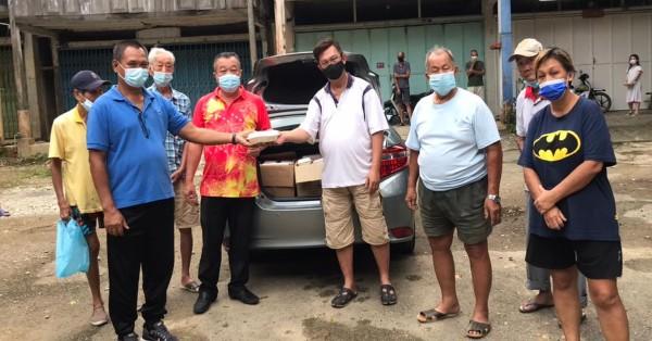 梁永康(左4)率领关丹斗母宫派盒饭义工移交盒饭予覃晓峰,由特伦斯(左2)代表移交。