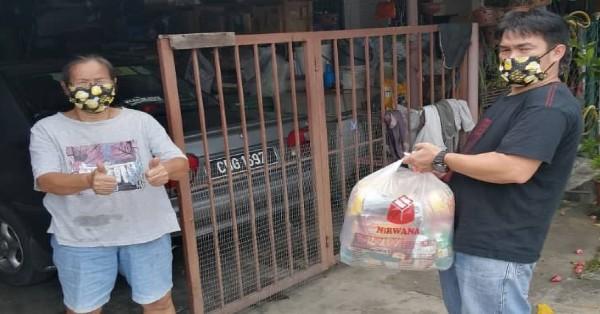 义工们逐户将粮食物资派到者手中。