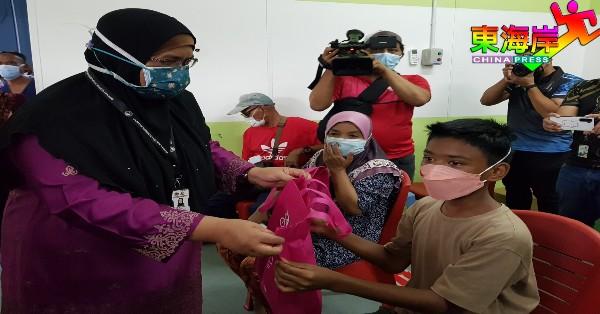 诺阿芝米(左)颁发小礼袋予参与疫苗接种居民及青少年。